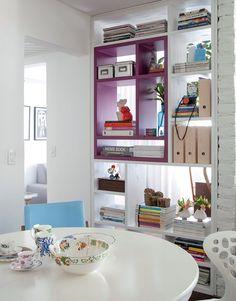 A arquiteta Marcela Madureira fazia questão de manter o quarto de hóspedes, mas queria integrá-lo ao living. A solução foi recortar a quina da parede: ela fechou uma parte com alvenaria e, na outra, fez uma estante com nichos de vários tamanhos