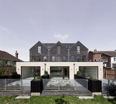 Denizen Works pairs black bricks with pointy panels for Whitstable housing