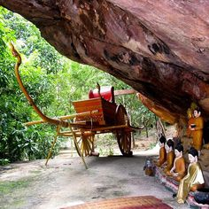 The Buddhist pilgrimage site of Lychee Hill at Phnom Kulen contains a large natural rock formation with a sacred reclining Buddha carved atop it. Here, beneath the rock are several smaller Buddhas and a golden ox cart. #phnomkulen #siemreap #cambodia #southeastasia #arachnid #instatravel #rtw #travelblogger #travelgram #goexplore #traveldeeper #mytinyatlas #wanderlust #takemethere #traveltheworld #travelpics #tourist #savoteur