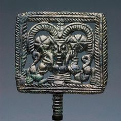 A TERMINAL OF A PIN WITH POTNIA THERON   H. 9 cm. Bronze Luristan, ca. 850-680 B.C.  A female (?) demon - a so-called Potnia Theron - stands in the centre of the open-work plaque and holds a stylized animal in each hand. The demon has an elongated face, protruding nose, beady eyes and short, upright ears. It wears a mighty horn-crown that dominates the upper part of the plaque. Rosettes beside the ears. Pin missing. A crack in the lower right part of the frame. Lower part of the frame…