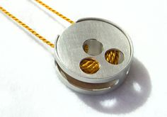 Follow the thread kinetic bobbin pendant:  Sterling silver kinetic pendant inspired by a bobbin and thread.    Sophie Stamp