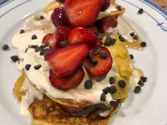 Homemade gluten free pancakes, fresh organic strawberries, dark chocolate chips, whipped cream, and local maple syrup.