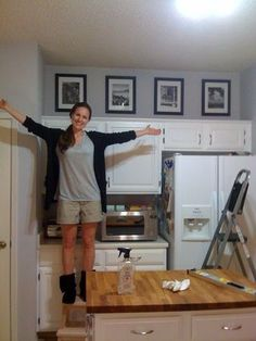 I always think of putting stuff on top but never hanging art  i love this! : Fill the annoying 'above cabinet' space in your kitchen w/black and whites of fave memories/defining moments - easy and good looking!