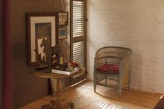 An antique side table and wicker chair make a cozy sitting area for a bedroom corner.