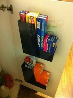 Magazine storage boxes attached to the inside of a cupboard door to hold plastic wrap, aluminum foil etc.