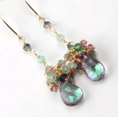 Stunning mystic topaz briolettes dangle beneath wire wrapped clusters of multicolored gemstones to create these unique, handmade gold dangle earrings. Beautiful, 11 mm mystic topaz briolettes are mounted on gold filled wires swaying bene. Topaz Earrings, Beaded Earrings, Earrings Handmade, Chandelier Earrings, Wire Jewelry, Bridal Jewelry, Beaded Jewelry, Jewellery, Gold Jewelry