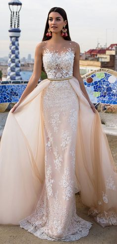 Alluring wedding gown Lina is a combination of classy organza, nude stretch satin and costly gauze. The lace bodice is manually embellished with beads, sequins and Swarovski crystals. An amazing long trail made of the organza and lace may be attached for the additional splendor.