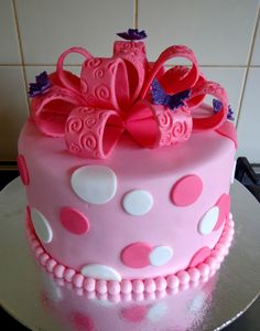 Pink cake with spots and fondant ribbon bow