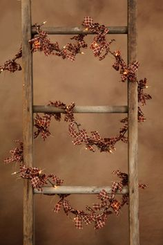 Prim Old Ladder...with a strand of Christmas lights...tied with pieces of homespun.