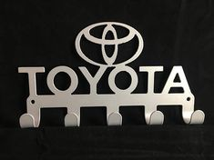 TOYOTA Key / Coat / Towel Rack CNC Plasma cut & powder coated with choice of colours and styles Mounts easily with two holes and have 5 hooks so you never loose your keys again. Dimensions: 213mm wide by 125mm tall Professionally finished in high quality Powder Coating. Please select
