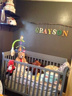 Grayson's bed bedding and his name on a branch we made