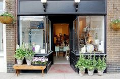 Dark grey painted shop front makes a great contrast to the green foliage.