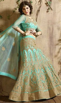 Do not be taken aback as you transform into a fairy tale princess as you are clad in this turquoise color net embroidered choli skirt. The fantastic attire creates a dramatic canvas with amazing lace, stones and resham work. #netlehengacholi #fancyalinelehangacolis #uniquestylelehengas