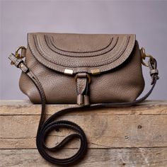 "Give any ensemble a subtle touch of Parisian panache. Chloe's Taupe Pouchette will see you fashionably through the holiday season and well beyond. In soft grained calfskin patterned with ripple-out seams, this petite pouch packs real fashion punch. Shoulder strap, 21½"" drop, Magnetic snap flap closure, One inside open pocket, Canvas lining, 7¾""W X 5""H X 3""D, ImportedAll sales are final."