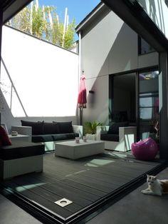 La terrasse extérieure est recouverte de lames composites de bois et ciment.