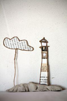 En papier :  au bord de la mer, le phare et son petit nuage