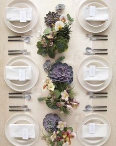 Petite earthy oases wend their way down the table, making for intriguing centerpieces. Succulents, lotus pods, air plants, and moss lay a foundation of green, purple, and gray shades. Lighter hellebore, fritillary, and lady-slipper orchids punctuate it. After your reception, pot the succulents in soil to decorate your newlyweds' nest and remind you of your special day for years to come.