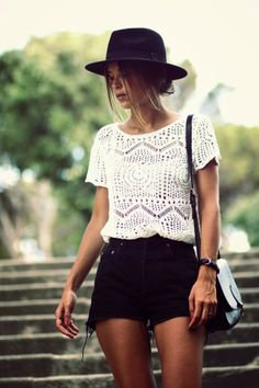 White lace haf sleeveless blouse with black skirt and black leather hand bag and black cap