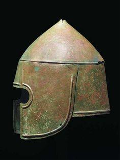 "An early Greek bronze Kegel Type helmet, the progenitor of the famous ""Illyrian Type"" helmet, c. According to archaeological evidence, the ""Illyrian type"" helmet evolved from the Kegelhelm (or Kegel type) of the Archaic Period found in Argos. Ancient Armor, Medieval Armor, Mycenaean, Minoan, Greek Helmet, Corinthian Helmet, Bronze, Arm Armor, Iron Age"