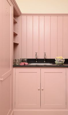 Pretty in Pink Laundry Room. Old Antique Rose Laundry Room Cabinets with Polished Granite Counters. DeVol Kitchens