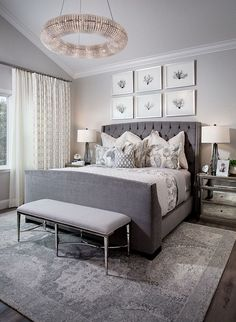 Grey tufted master bedroom bed with six picture frames above it. Pretty!