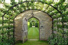 Bewachsener Bogen mit Steinmauer und Tür