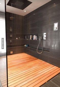 Área para chuveiro ampla e com piso de madeira.