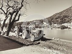Photo about A vintage image of workers with old tractor and dump trailer building up the sides of a road along Ganges River in Rishikesh. Image of image, workers, dump - 83288982 Image Photography, Editorial Photography, Dump Trailers, Rishikesh, Vintage Images, Old World, Tractors, India, River