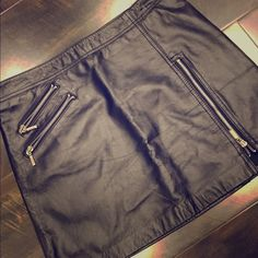 BEBE Leather Skirt Black leather skirt from BEBE. Has zipper pockets and a zipper on the side. Has a black lining underneath and zips on the side. 31 in around the waist and about 15 in from top to bottom. 100% leather lining is 100% Acetate bebe Skirts Mini