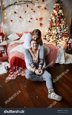 christmas couple Pretty couple is hugging on by the sofa with Christmas presents in the boxes