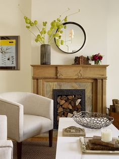 For a perfectly styled mantel, create a balanced and curated composition. We see only a tall flower vase, a round mirror and a small cluster of objects here. That trio offers a strong geometry, with different shapes arranged to form a larger triangle and an organic feel. Yet the mantel is edited, and the objects are carefully presented. Extra points for the stacked firewood below