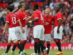 Manchester United players laugh and smile as they congratulate Saha (centre) for opening t...