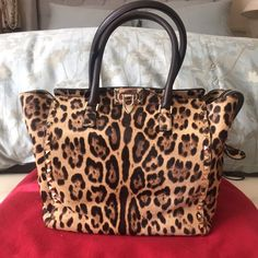 """Valentino Leopard Print Hair Rockstud Handle Bag Authentic Valentino Garavani Rockstud double handle bag in leopard print calf hair. Gold-finish studs. Metal flip lock closure and zip closure. Detachable studded shoulder strap, linen/canvas lining. Internal zip pocket and double open pocket for cell phone. Rolled tote handles, extended zip top secures at side tab. 10""""H x 14""""W x 6"""" D. Made in Italy. One flaw, pictured: some of the hair has worn down on a bottom corner of the bag--not visible…"""