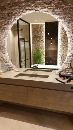 Stunning modern bathroom with a large round LED mirror combined with a Diresco Belgian Sand quartz composite sink