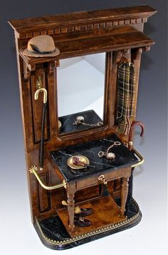 Victorian Hall Stand with  a camel fedora, Burberry scarf, pipe in an ash tray, pocket watch with fob. The table top is black marble  and take note of the black tassle on the key for the drawer. A pair of men's shoes and a pair of umbrellas complete the scene