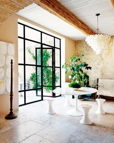 Iron frame of windows and doors leading outside, white modern dining space, and modern chandelier