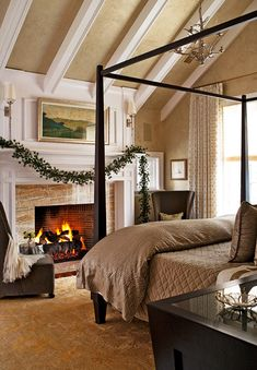 A gold and taupe Oushak rug balances the cool grey and taupe fabrics in the master bedroom of the Bloomfield Hills home designed by architect Alexander Bogaerts and interior designer Lucy Earl. A simple garland of evergreens contrasts with the white fireplace. White rafter beams create a crisp contrast with beige. Source: Traditional Home Magazine image