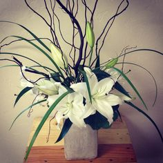 These huge oriental lilies, grass and twigs form a gorgeous and modern arrangement.