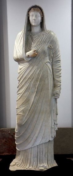 Roman full-length portrait of a matron with the addition of a head of Livia Drusilla (58 BCE-29 CE), wife of the Roman emperor Augustus. Shown freestanding, in contrapposto stance, of white marble. Discovered in the peristyle of the Villa of the Mysteries (Pompeii), now on display in the Antiquarium (Museum) di Boscoreale. An outer cloak (palla) is shown draped over the head and shoulders; it covers the full-length stola, visible underneath. When first discovered more of the painted…