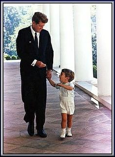 Actual photograph of John F. Kennedy and his son, John, Jr as they happily walk the grounds of the White House.