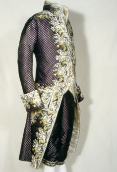 Court Suit, 1770-1785, French, silk, velvet, satin, cotton. Purple velvet coat and breeches, lavishly embroidered with naturalistic flowers; white satin waistcoat, similarly embroidered. Belonging to Sir John Stanley of Alderley Bt. Gentleman of the Privy Chamber to George III.