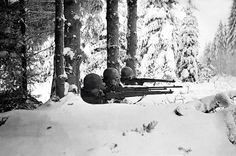 Three US infantrymen in the snow during the Battle of the Bulge, Ardennes, Belgium, World War II, January 1945.