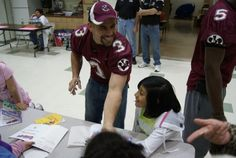 Veteran Racine Raiders wide receiver Sam D'Alie enjoys the opportunity to sign an autograph for a student at Julian Thomas Elementary School as part of the Reading with the Raiders program.