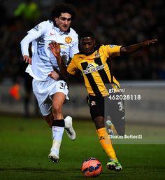 Sullay Kaikai of Cambridge United battles for the ball with Marouane Fellaini of Manchester United Cambridge United, Manchester United, Battle, Soccer, The Unit, Football, Baseball Cards, Sports, Hs Sports