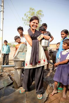 Najma Khan laughs as she collects water with others in Churbara village, India. Najma runs a dress-making business with some friends; she also teaches younger girls in her village some basic sewing.