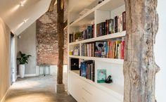 De achterzijde van het witte volume in de woonvoerder bevat boekenkasten. Dit is het smaltse gedeelte van de plattegrond in de woonkamer.