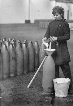 A munitions worker filling a shell at the National Filling Factory at Banbury, England