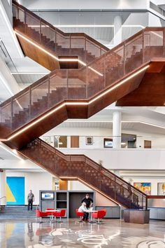 A grand staircase with perforated metal railings zigzags up through the four-storey atrium in a new university building in Kansas by Gensler.