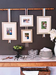 ~ i love the idea of these hanging  picture frames; especially the bamboo stick!!  Possibly would use darker color for frames, but the idea is pretty neat ~