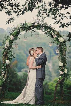 wedding photo shoot bride and groom kiss near wedding arch alyssa maloof photography